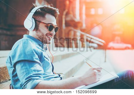 Find inspiration. Cheerful content smiling young man drawing and listening to music while sitting on the footsteps