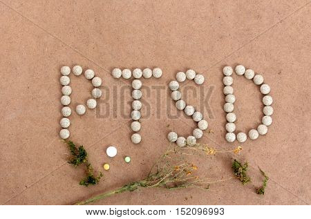 picture of a PTSD text with herbal pills on a wood background