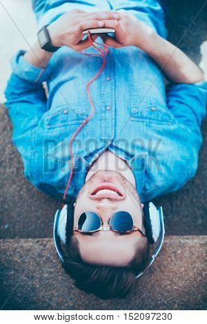 Open up new world. Positive content smiling man using cellphone and listening to music while lying on the footsteps