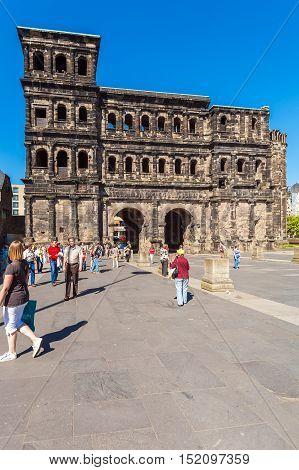 Trier, Germany - April 7, 2008: Tourists Walk In Front Of Porta Nigra