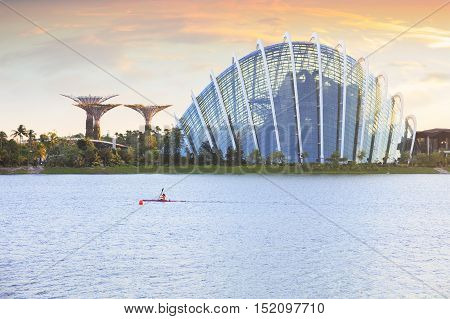 Singapore, Republic of Singapore - May 4, 2016: Woman on kayak crossing Marina Bay at sunset. Supertree grove and Cloud garden on background