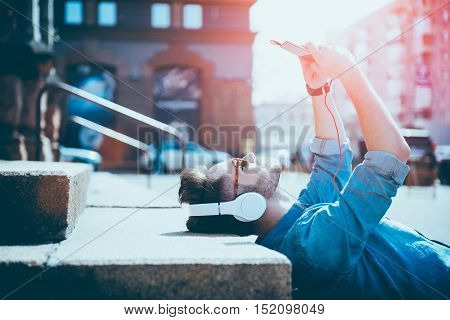 Bright days. Joyful content smiling young man lying on the footsteps and using cell phone while listening to music