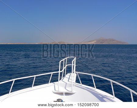 front part of white yacht boat sailing in blue Red sea towards earth mountains