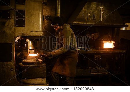 Blacksmith forging the molten metal on the power hammer in smithy