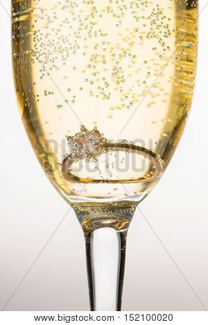 Engagement Ring in Champagne Glass on Grey Background