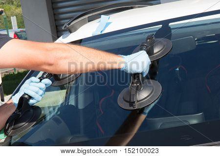 Mecanic Man Is Changing Windscrenn On A Car