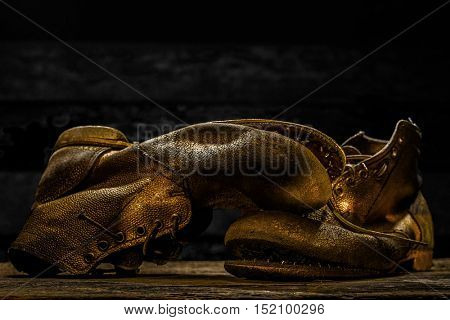 Old boots worn with scratches and untied shoelaces on dark background