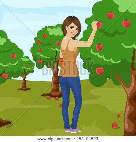 full length portrait of young brunette woman picking red apple from tree in the orchard