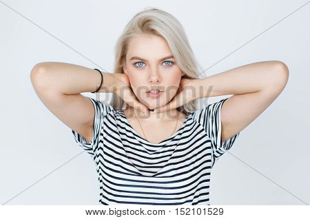 Close-up awesome caucasian attractive female model with blond hair posing in studio wearing striped shirt and, isolated on grey background