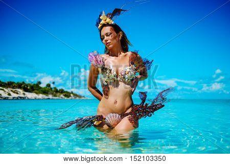 Portrait of exotic fantasy mermaid in blue ocean
