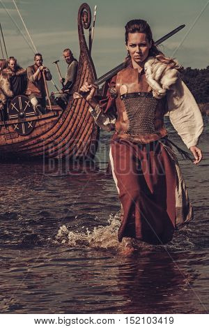 Confident viking woman with sword walking along the shore with Drakkar on the background