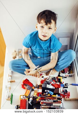 little cute preschooler boy playing lego toys at home happy smiling, lifestyle children concept close up poster