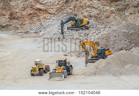 Group of yellow machines working at gravel pit