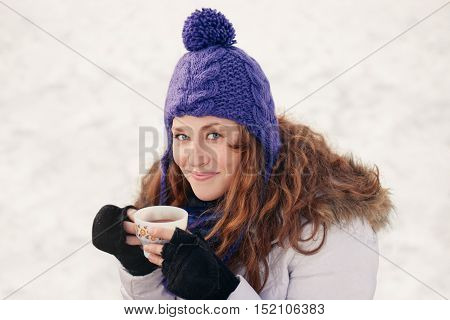 Millenial girl sipping hot chocolate in a snow filled park