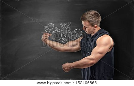 Fruits pictured on a black background and a fitness man showing his bicep under the picture. Proper nutrition. Gaining muscle mass. Keeping on a diet.