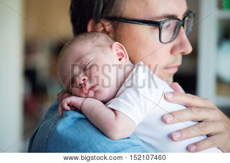 Close up of young father holding his newborn baby son in his arms