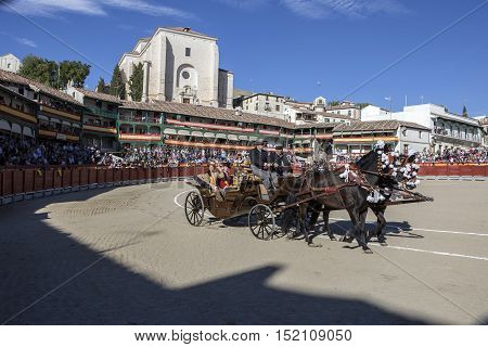 Chinchon Spain - October 15 2016: Traditional bullfighting stamp Horse Cart with the maids of honor of the bull events in the plaza mayor of chinchon during the festival benefit Chinchon Madrid province Spain