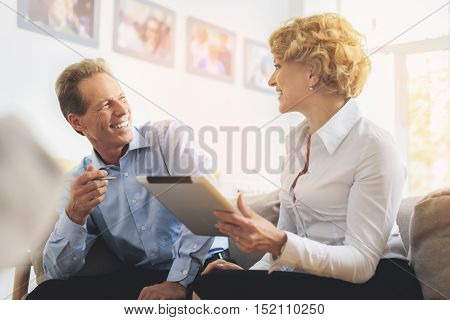 Friendly colleagues are talking and smiling. They are sitting on sofa in lounge room. Woman is holding tablet