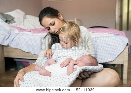 Young mother holding her little two year old girl at home sick with chickenpox rash and her baby son