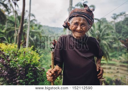Portrait of senior woman standing with a cane and smiling. Old female with beautiful smile on her face outdoors in countryside.