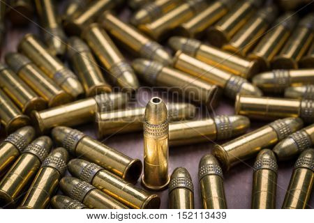 Selective focus on a single 22 caliber rimfire ammunition bullets for a rifle poster