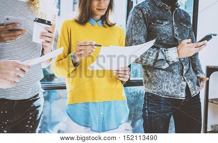 Group of coworkers friends standing front of the window in the office and discussing business idea.Young woman holding a papers in her hands, man using his smartphone. Blurred, horizontal