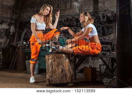Sexy Blacksmith Women In Orange Pants Are Talking On The Workshop Background.