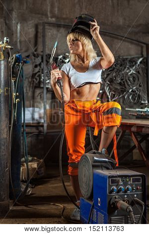 Blond Sexy Welder Woman In The Protective Mask.