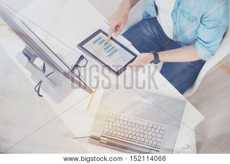 Be a workaholic. Concentrated hardworking ambitious man working as a programmer holding a tablet while using computer and laptop in an office.