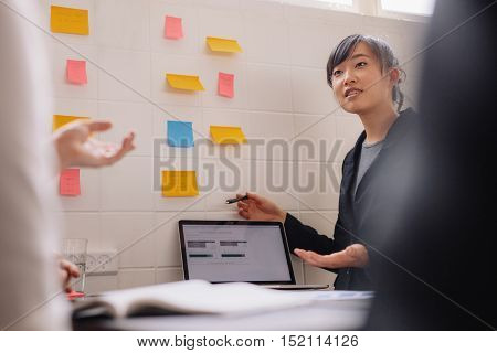 Asian businesswoman presenting her new ideas on laptop and adhesive notes on wall. Young female executive giving presentation to coworkers.
