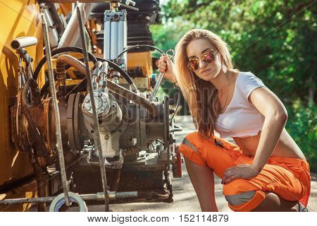 Sexy Woman Worker Is Repairing Tractors Engine With The Wrench.