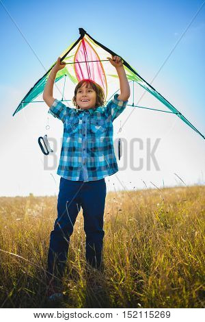 Happy and smiling boy playingin with kite outdoor.