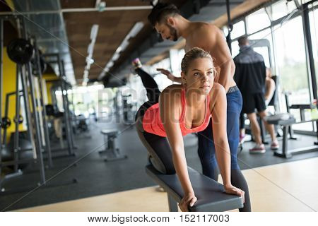 Personal young trainer helping woman in gym