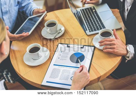 Close up of business colleagues discussing project in cafe. They are sitting at table and drinking coffee. Woman is pointing at document. Man is using tablet