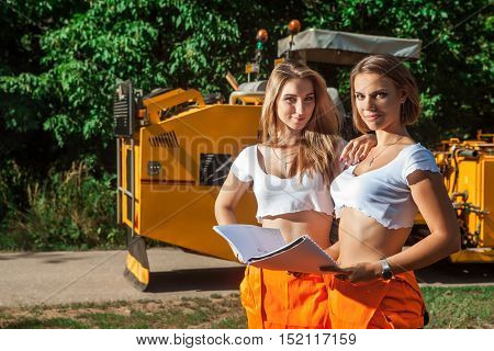 Two Women Workers With The Road Schemes Are Looking At The Camera. Tractor On The Background.
