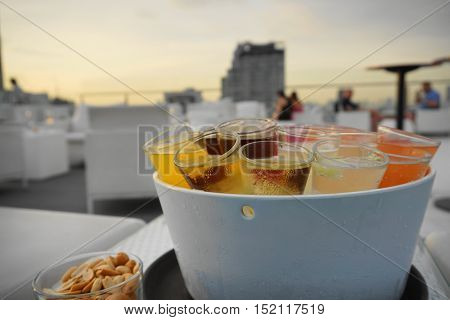 rainbow cocktail shotes serve in ice bucket in evening twilight nature light with background as business men hangout with friends - backlight pic with soft and select focus