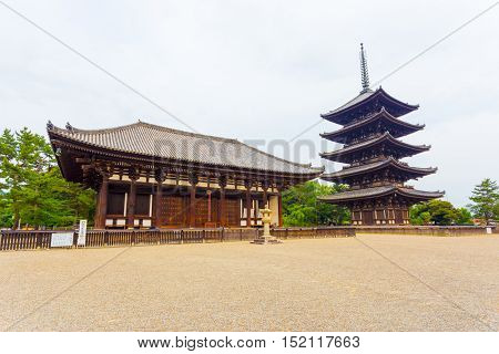 The front of the East Golden Hall To-kondo and five story pagoda Goju-no-to part of Kofuku-ji Buddhist temple on an overcast day in Nara Japan. Horizontal copy space poster