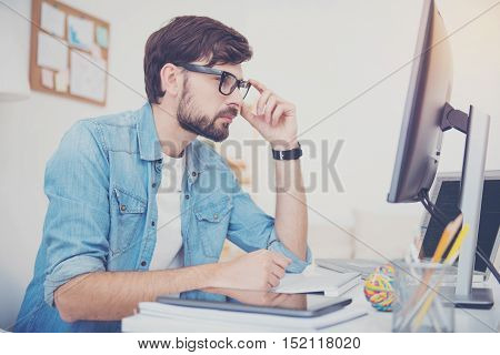 What is the problem. Handsome concentrated successful programmer working in an office while coding and looking at the computer monitor attentively.