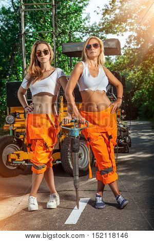 Two Sexy Women Workers In Overalls With The Jackhammer.