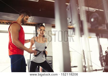 Personal handsome trainer helping woman in gym