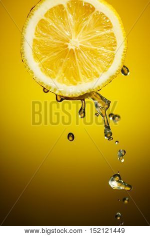 One half of lemon with fresh water drops isolated on orange background