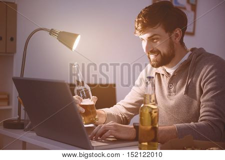 Rest from work. Handsome young smiling man playing computer games using a laptop while drinking beer after working day.