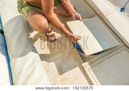 Cognac, France - July 22, 2013: A retired man in shorts and topless takes care of the maintenance of his private swimming pool. Maintenance of the pumping system of a pool