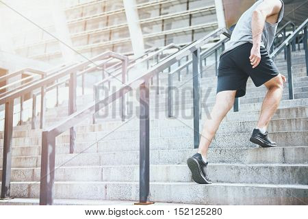 Move on. Active enthusiastic athletic man wearing sportswear and climbing up the stairs before training.