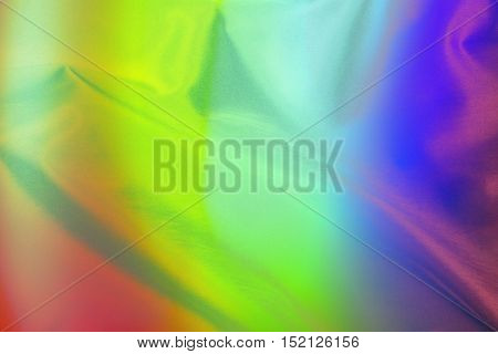An abstract background of a soft satin cloth in rainbow colors