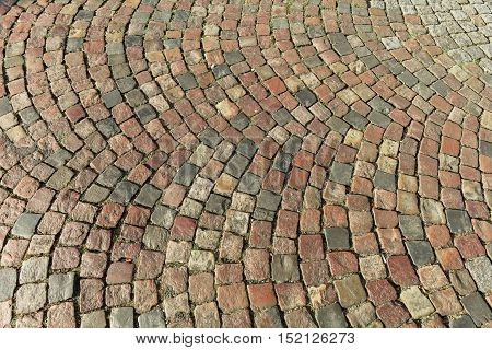Street paved with cobblestone. Urban stone paving stones. Stone road texture. Ancient cobblestone road. Abstract background of old cobblestone pavement. Paris France