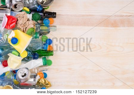 Rubbish that can be recycled on wooden background with copy space