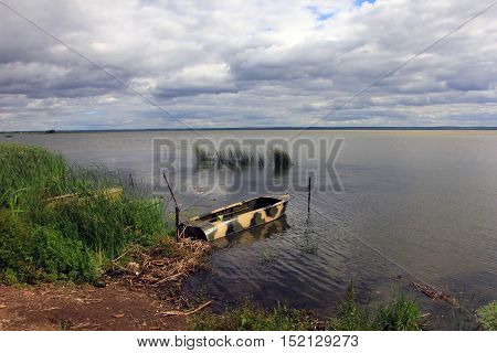 metal boat camouflage colors at the shore of a large lake Nero in summer and the reeds in the water
