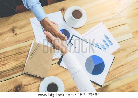 Great deal. High angle shot of two businessmen shaking hands on wooden table in office