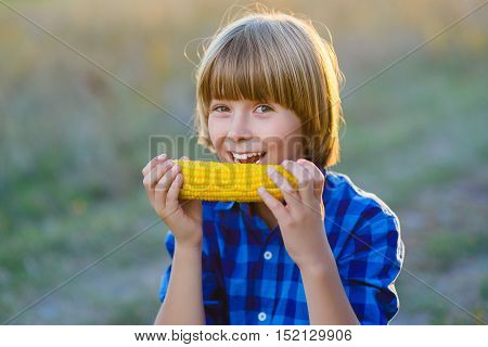 Happy boy eating healthy corn on the cob.